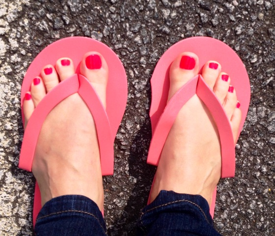 Brightly colored pink toes against the sunny pavement backdrop.